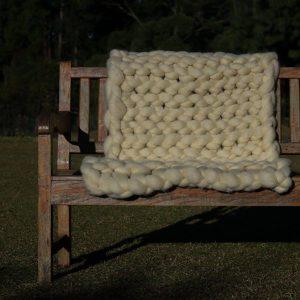 Manta em maxi tricot gigante da lã natural feitas no tricô de braço.