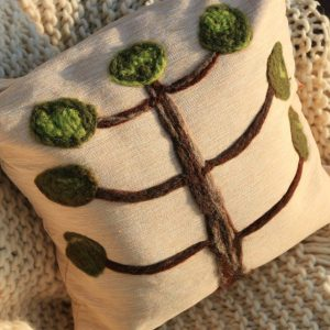 Almofada araucária em feltragem de lã natural, sobre uma capa de tecido 100% algodão com fechamento em zíper.