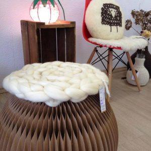 Banqueta em papelão reciclado, em formato de bola com assento em lã natural desenvolvido em maxi crochet ou crochê gigante.