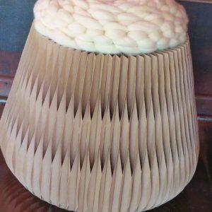 Banqueta em papelão reciclado, em formato de trapézio com assento em lã natural desenvolvido em maxi crochet ou crochê gigante.